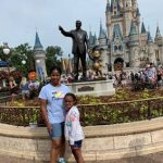 Girl with cerebral palsy in front of Cinderella's Castle at Disney World
