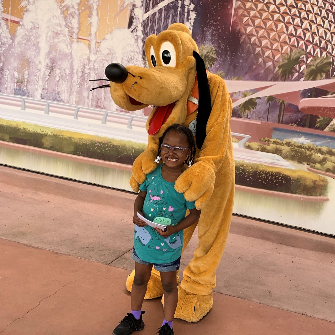 Girl with cerebral palsy smiling with Goofy from Disney World