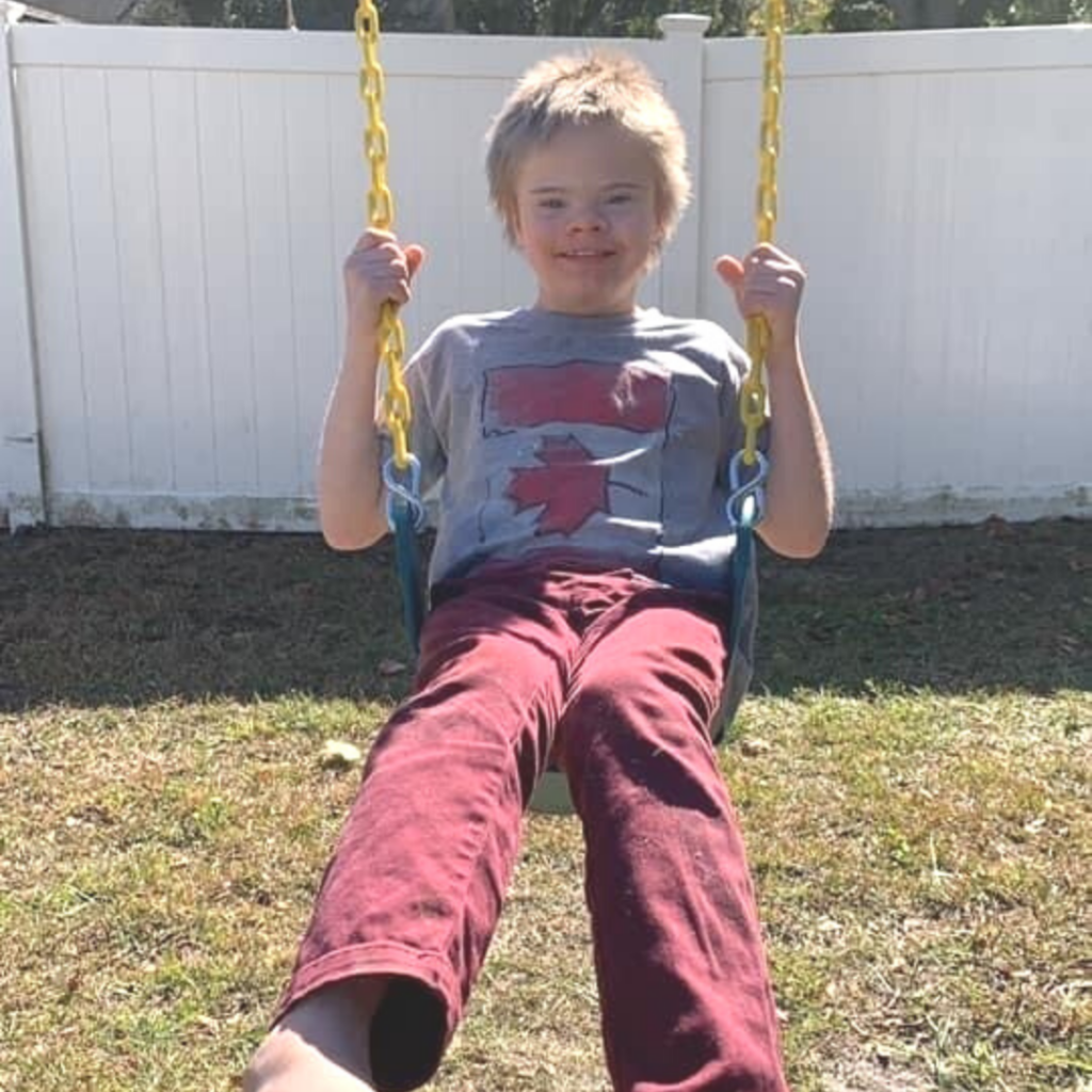 Boy with Down syndrom enjoying his new swing
