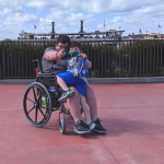 Teen boy with Chiari malformation with younger brother entering Disney