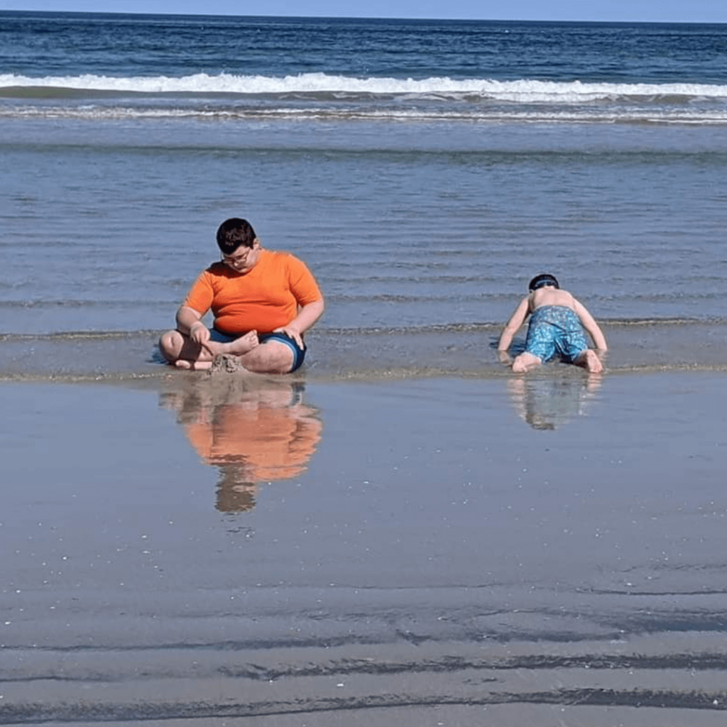 Teen boy with Chiari malformation playing at the beach with younger brother