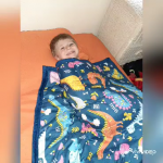 Boy with hearing loss under a weighted blanket