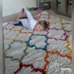 Boy with hearing loss laying on a fuzzy carpet
