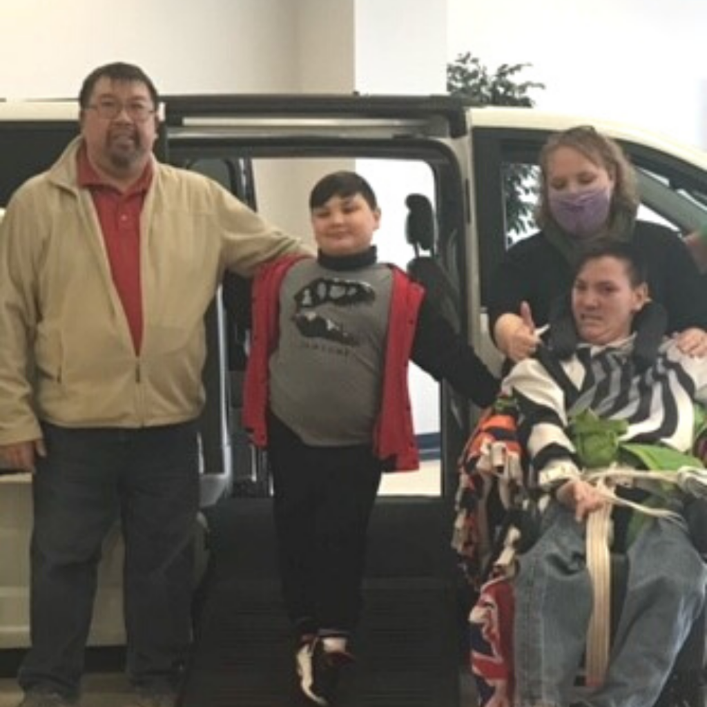 Teen with cerebral palsy in front of new accessible van