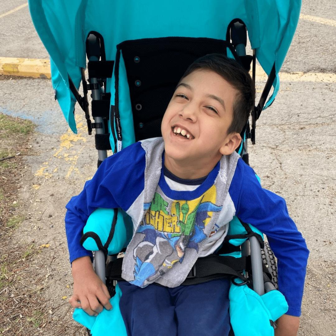 Boy with cerebral palsy enjoying new new adaptive stroller
