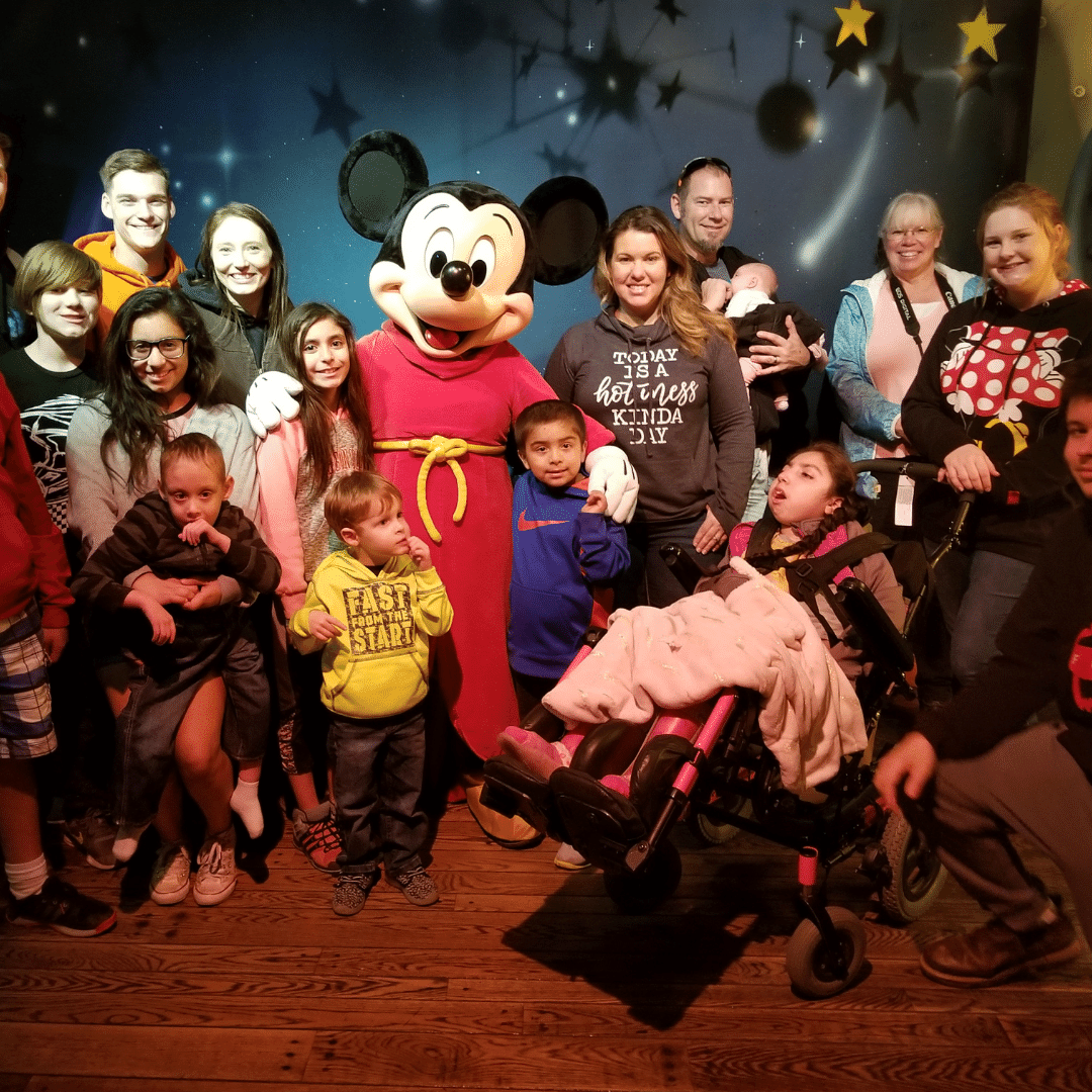 Girl in wheelchair with Mickey Mouse and her family