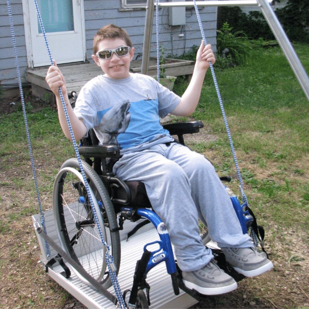 Teen boy enjoying backyard wheelchair swing