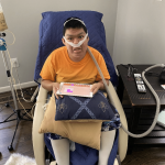 Teen boy receiving oxygen while getting relief from massage chair