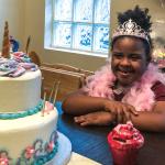Girl wearing tiara looking at unicorn cake