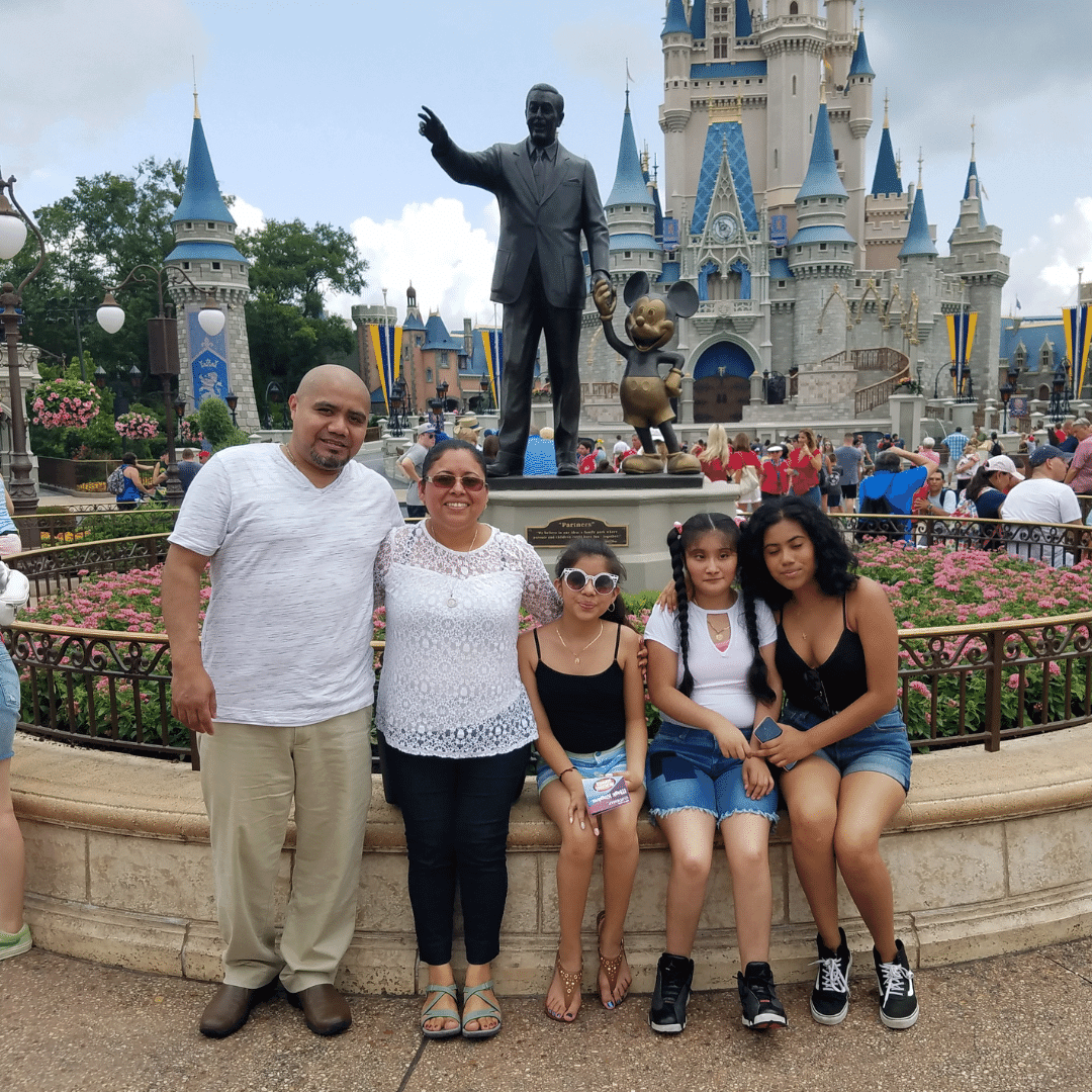 Family smiling in front of Cinderella's Castle at Disney World